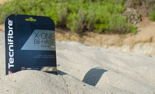 A photograph of the the front of Tecnifibre X-One Biphase in the sand at the beach on a sunny day.