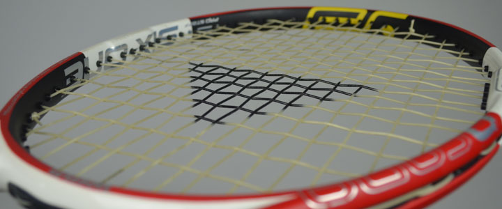 An angled photograph of a tennis racquet strung with Tecnifibres X-One Biphase including the triangle Tecnifibre stencil on the strings.
