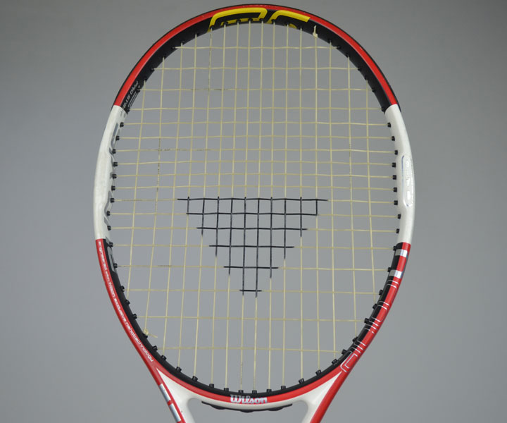 A photograph of the front of a tennis racquet strung with Tecnifibres X-One Biphase including the triangle Tecnifibre stencil on the strings.