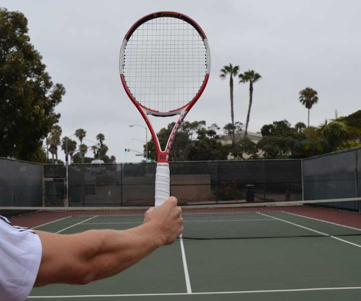 A photograph showing a tennis racquet being held out in front with the incorrect tennis serve grip.
