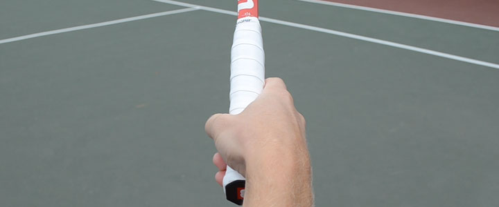 A photograph of my right hand holding the proper tennis serve grip with a tennis court in the background.